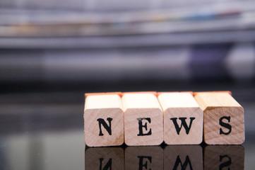 """Holzbuchstaben auf Hintergrund """"NEWS"""" neuigkeiten"""