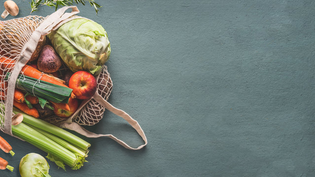 Various farm organic vegetables from local market in net string reusable bag on rustic background, top view with copy space for your design, banner. Clean and healthy food concept