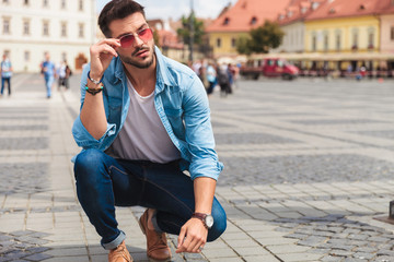 curious casual man crouching in the city fixes red sunglasses