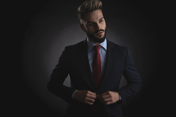 portrait of curious businessman buttoning navy suit while standing
