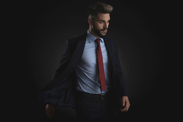 sensual businessman in navy suit looks to side
