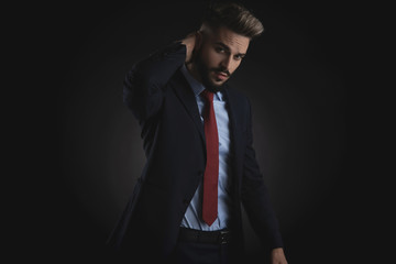 portrait of young businessman holding back of head