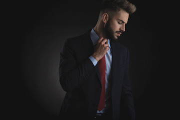portrait of businessman looking down to side and fixing tie