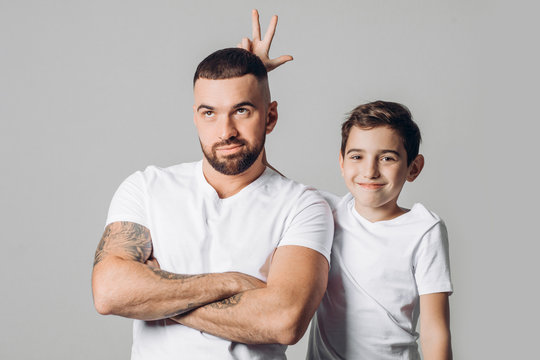 funny son holding his hands on his unhappy daddy's head close up photo. isolated grey background.kid having fun with elder brither