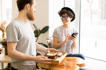 Cheerful excited young lady customer in black hat and eyeglasses sitting on window-sill and listening to music in earphones while smiling at waiter who bringing coffee and doughnut to her.