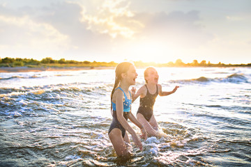 swimming in the ocean of two young girls on a sunny day