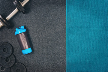 Fitness or bodybuilding concept background. Product photograph of old iron dumbbells on black grey, conrete floor in the gym. Photograph taken from above, top view with lots of copy space