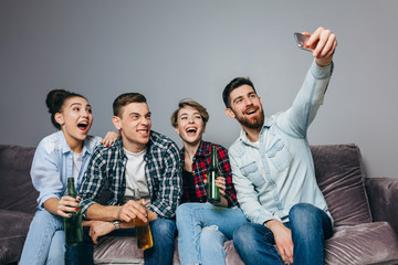 cheerful friends are sitting on couch taking selfie picture. close up photo. lifestyle, free time