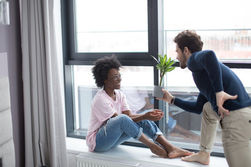 Loving happy interracial couple sitting on the sill and looking at the large window in their hired flat. Caucasian guy wears a dark poolover, african girl wears pink shirt.