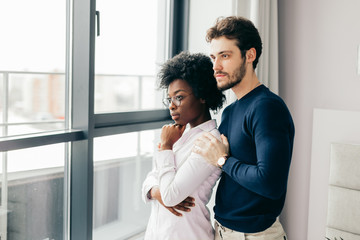 Positive african woman embraces with her european handsome brunette boyfriend, relaxing at home, give warm hug to each other, stand near window background. Multiethnic relationship and love concept.