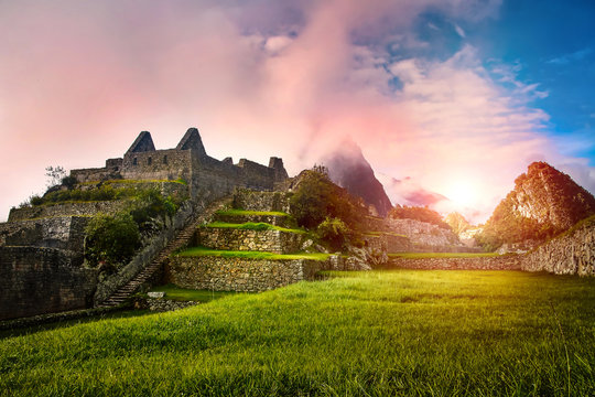 Scenic landscape of the stone ruins Machu Picchu at sunrise. Huayna Picchu mountain in the clouds in the background