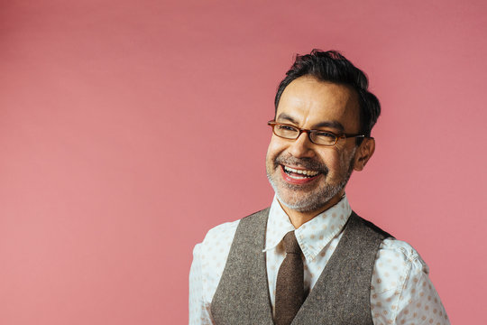 Portrait of a smiling mature man in vest and glasses, isolated on pink