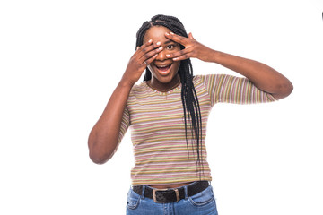 Closeup portrait of a young woman shy and flirting with hands covering entire face except one wide open eye looking at camera,isolated on a white background. Negative human emotion facial expressions