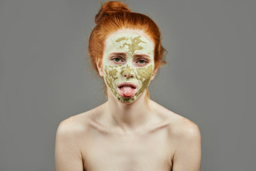 young woman with green mask feels bored. close up photo. nervous girl with mud mask showing tongue