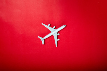Miniature toy airplane on red background. Trip by airplane.