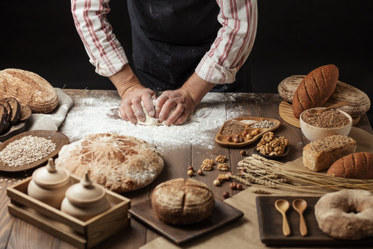 Hands of male chef cook working with dough, surrounded by bread and long loafs from whole wheat flour. Bakery concept. Homemade bakery concept