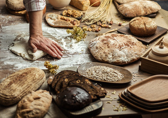 Hands kneading raw dough on table. Top view on baker workplace, working with pastry, all surface on flowered table is occupied with loaves of bread and ingredients. Culinary, cooking, bakery concept
