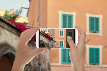 A tourist is making a photo of street in the Trastevere area with red flowers on the roof of a building in Rome, Italy on a mobile phone