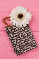 Big white daisy flower and shopping bag. Pink wooden background.