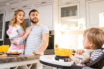 Portrait of happy family enjoying breakfast in kitchen, focus on young parents looking at baby sitting in kid chair, copy space