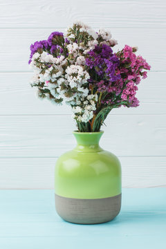 Green ceramic vase with colorful statice limonium flowers. Blue wooden background.