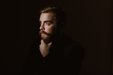 Sepia portrait of a pensive man with a beard and stylish hairdo dressed in the black shirt on the dark background
