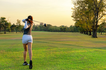 Healthy Sport. Asian Sporty woman golfer player doing golf swing tee off on the green evening time, she presumably does exercise.  Healthy Lifestyle Concept.
