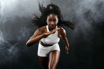 Strong athletic black skin woman sprinter, running on background with smoke wearing in the sportswear. Fitness and sport motivation. Runner concept with copy space.
