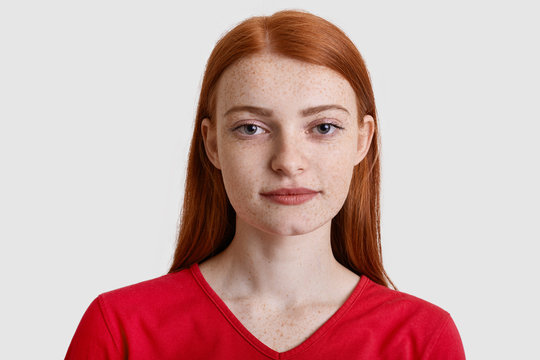 Headshot of attractive red haired European woman with freckled skin, looks seriously at camera, has minimal make up, wears red sweater, isolated over white background. Natural beauty concept