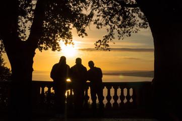 Tre amici ammirano il tramonto