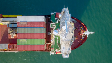 Aerial image of a large container ship at sea, loaded with various container brands