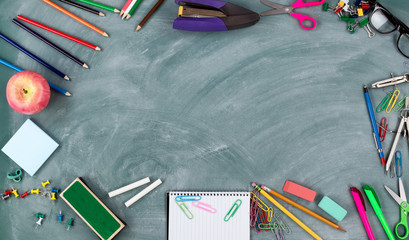 Back to school concept with green chalkboard and a variety of student supplies in circle border