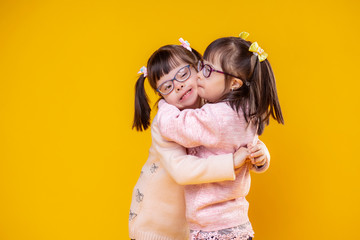 Charming positive sisters with chromosome abnormality hugging each other