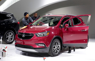 Auto show workers detail a General Motors Buick Encore SUV before press days of the North American International Auto Show in Detroit