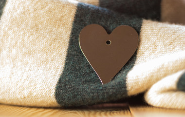 Close-up: image of silver heart decoration is on a beautiful warm striped knitted scarf. Concept: Valentine's Day.
