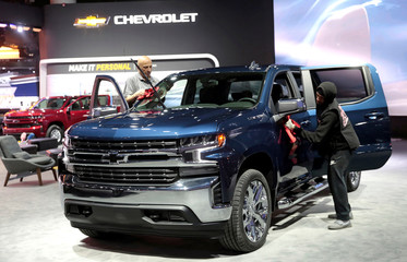 Auto show workers detail a General Motors 2019 Silverado pickup truck before press days of the North American International Auto Show in Detroit