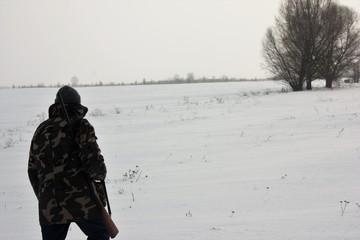 hunter walking on the snowy field in winter