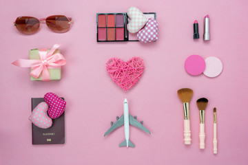 Table top view accessory of clothing women to plan travel in valentine's day background concept.Passport & clothes with many essential love items in holiday season.Several cosmetics on pink paper.