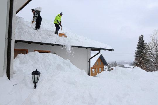 Zwei Männer schaufeln hohen, schweren Schnee von einem Hausdach