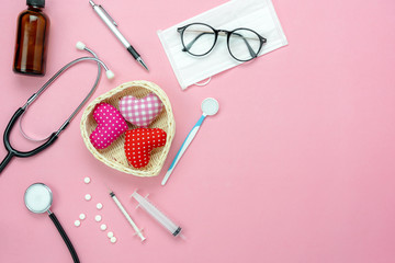 Table top view aerial image of accessories healthcare & medical with Valentines day background concept.Essential instruments or equipment on pink paper.Flat lay  items for doctor using treat patient.