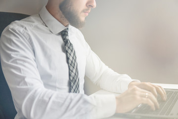 Light background. Close up. Smartphone in hand Young bearded businessman. Financial business. Office work with a laptop. Businessman work with computer on table in office work.