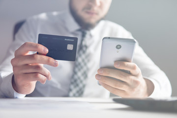Young businessman with a bank credit card in his hands. Smartphone and Internet Commerce. Payment of goods online. Online payments through the phone. Online trading on the currency exchange.