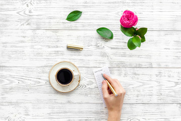 Home work desk, feminine workplace. Notebook and stationery near pink flowers and coffee on white wooden background top view