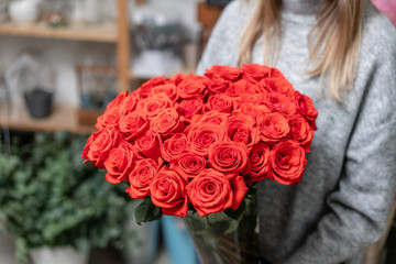 Red roses in glass vases in womens hands. Bunch scarlet red. the concept of a florist in a flower shop. Wallpaper.
