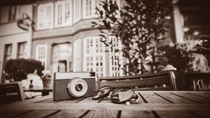 Old camera and sunglasses on a wooden table on the street. Bremen, Germany. . Image in sepia color style
