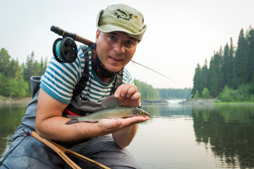 Happy angler with grayling fishing trophy