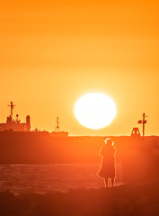 Fuzzy silhouette of woman taking picture of red sunset in a harbor.