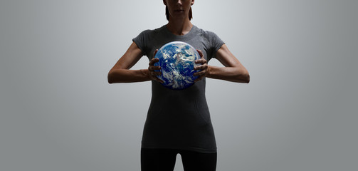 Empowered fit woman holding world in her hands