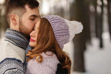 Winter, couple in love. Young man and woman in knitted winter wear embracing and kissing in snowy forest. Romantic couple enjoying snowfall. Love story in the winter forest