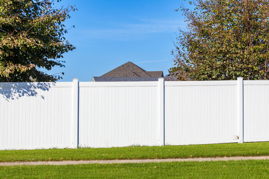 White vinyl fence spanning across the back yard of a home
